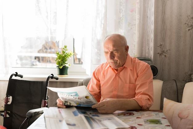 Close-up sentado feliz homem sênior lendo artigos do jornal branco relaxando na sala de estar.