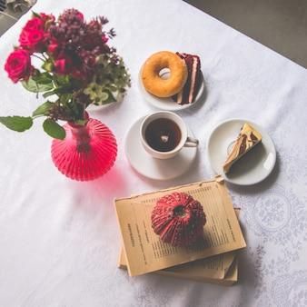 Close-up servindo pratos na mesa: chá, rosquinha, um pedaço de bolo, flores em um vaso, velas, livros. ver acima