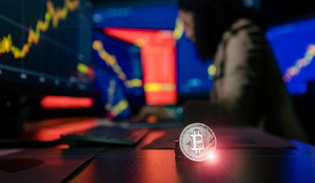 Close-up shot da criptomoeda bitcoin com flare na frente do investidor corretor asiático feminino