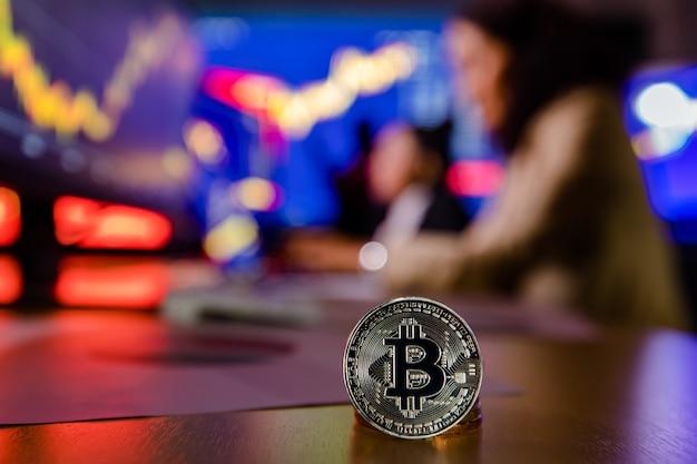 Close-up shot da criptomoeda bitcoin em frente ao computador do investidor feminino da corretora asiática