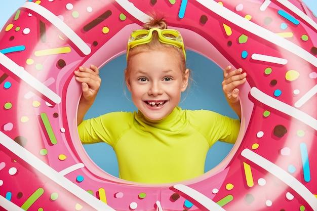Close up shot da linda ruiva alegre garotinha usa óculos de natação na cabeça, olha através de uma natação de borracha rosa, tem largo sorriso, falta de dentes, aproveita os últimos dias de verão quente, dia ensolarado