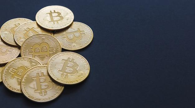 Close up shot de alguns bitcoins em um fundo azul escuro e copie o espaço