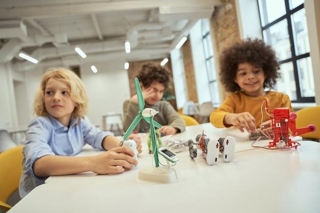 Close up shot de brinquedos técnicos cheios de detalhes sobre a mesa de crianças sentadas à mesa e