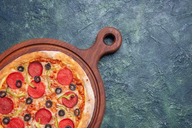 Close-up shot de deliciosa pizza em uma tábua de madeira no lado direito em uma superfície azul escura com espaço livre