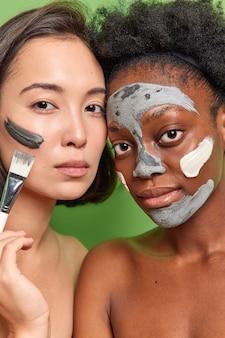 Close up shot de diversas jovens aplicando máscaras de argila no rosto, segurando escova cosmética, olhando diretamente para o suporte da câmera, sem camisa, dentro de casa, cuidar da tez e da pele isolada sobre a parede verde