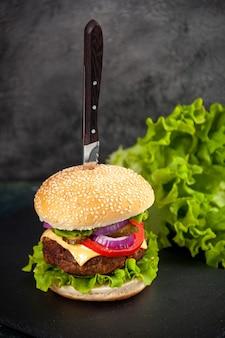 Close up shot de faca em delicioso sanduíche de carne e verde na bandeja preta do lado esquerdo em superfície desfocada com espaço livre