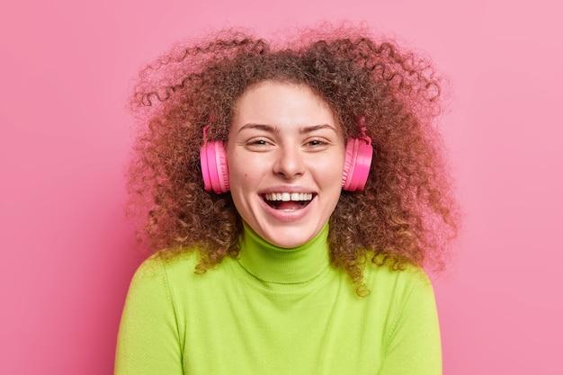 Close up shot de mulher de cabelo encaracolado radiante ri e sorri amplamente tem cabelo crespo espesso ouve música por meio de fones de ouvido estéreo sem fio vestida com gola verde isolada na parede rosa