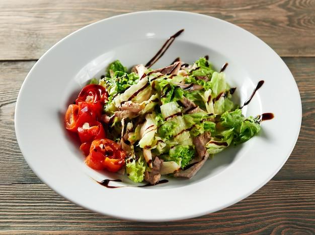 Close up shot de salada picada misturada com carne de frango fatiada decorada com molho