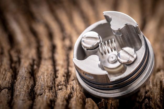 Close-up shot de single space coil em atomizador de gotejamento reconstruível de ponta para caçador de sabores em fundo de textura de madeira natural rústica, dispositivo de vaporização