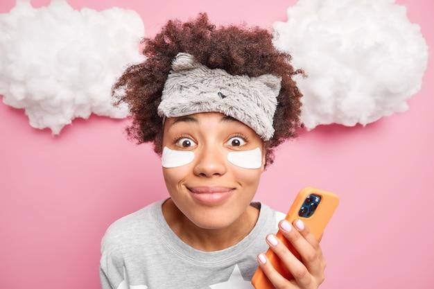 Close up shot de sorrindo satisfeita linda garota afro-americana olhando alegremente para frente usa telefone celular para bater papo on-line desfruta de ambiente doméstico usa pijama com máscara de dormir.