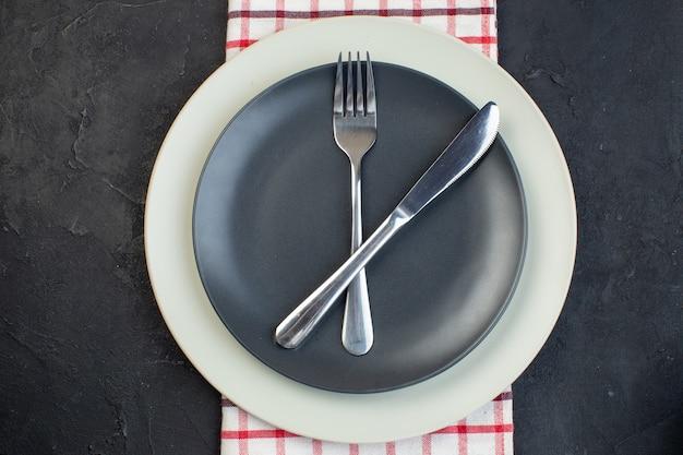Close up shot de talheres definido em cor cinza escuro e pratos vazios brancos em toalha vermelha listrada em fundo preto com espaço livre
