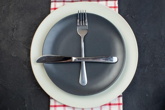 Close up shot de talheres definido em cor cinza escuro e pratos vazios brancos em uma toalha vermelha listrada em fundo preto