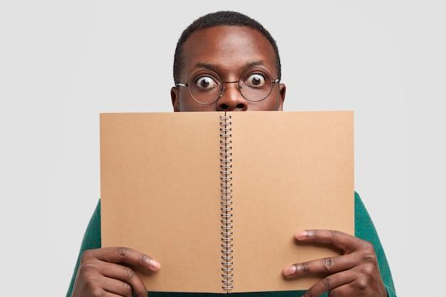 Close up shot de um homem negro chocado cobrindo o rosto com um bloco de notas em espiral, se sentindo surpreso, modela o fundo branco do estúdio, lê anotações escritas no caderno