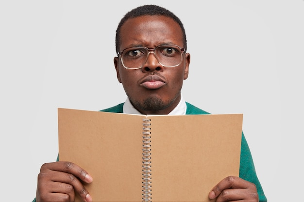 Close-up shot de um jovem afro-americano descontente com uma expressão facial sombria, franzindo os lábios, segurando o bloco de notas em espiral