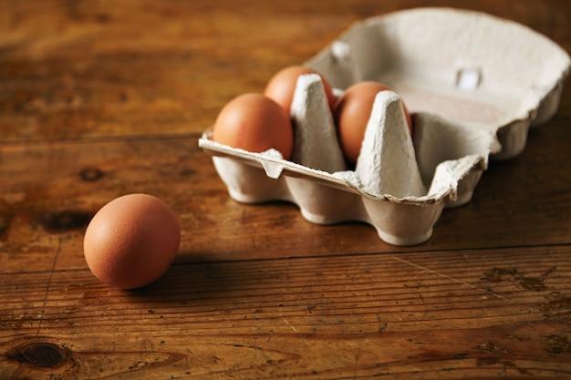 Close-up shot de uma caixa de ovos reciclável aberta com 3 ovos dentro e um ovo próximo a ela em uma mesa de madeira granulada marrom