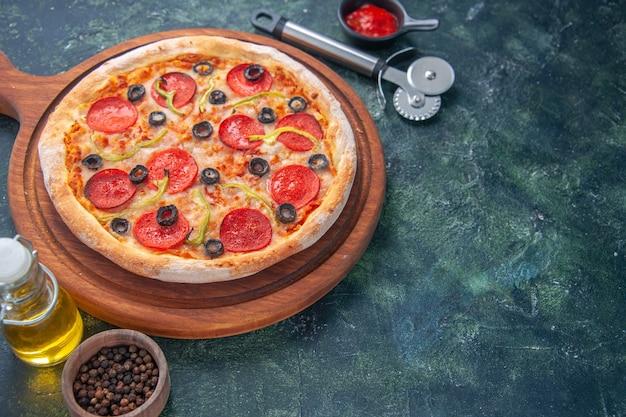 Close-up shot de uma deliciosa pizza caseira em uma tábua de madeira com tomates e óleo de garrafa de ketchup de pimenta no lado direito em uma superfície escura