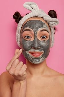Close-up shot de uma linda mulher asiática aplicando máscara purificadora preta no rosto, fazendo tratamentos de beleza, fazendo um sinal coreano, usando bandana cinza, ficando sem camisa contra a parede rosa do banheiro