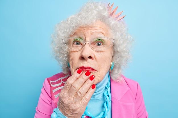 Close-up shot de uma mulher aposentada de cabelos grisalhos maravilhada mantendo a mão no queixo parece surpreendente