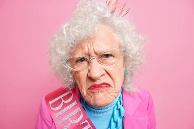 Close up shot de uma mulher enrugada descontente com um sorriso afetado, o rosto parece infeliz, tem uma maquiagem brilhante e está descontente com alguma coisa