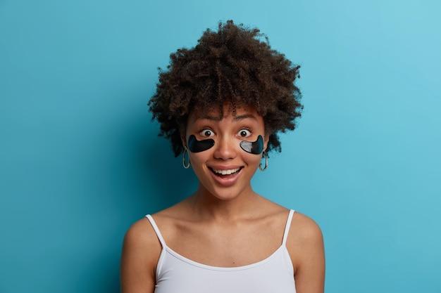 Close-up shot de uma mulher feliz de pele escura tem terapia de olho anti-envelhecimento, aplica adesivos cosméticos sob os olhos, quer ter uma pele saudável, vestida com roupas casuais, isolada sobre a parede azul
