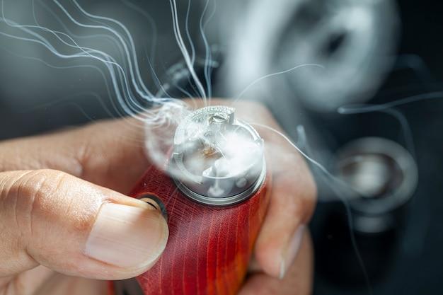 Close up shot show burning of e juice or e líquido na única micro bobina, fio e algodão dentro do atomizador de ponta em mods de caixa de madeira estabilizada natural vermelha para vaping