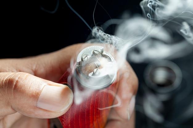 Close up shot show burning of e juice or e líquido on single micro coil, wire and cotton dentro do atomizador high-end em mods de caixa de madeira estabilizada natural vermelha para vaping