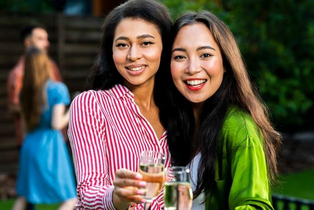 Close-up smiley meninas jovens com taças de champanhe