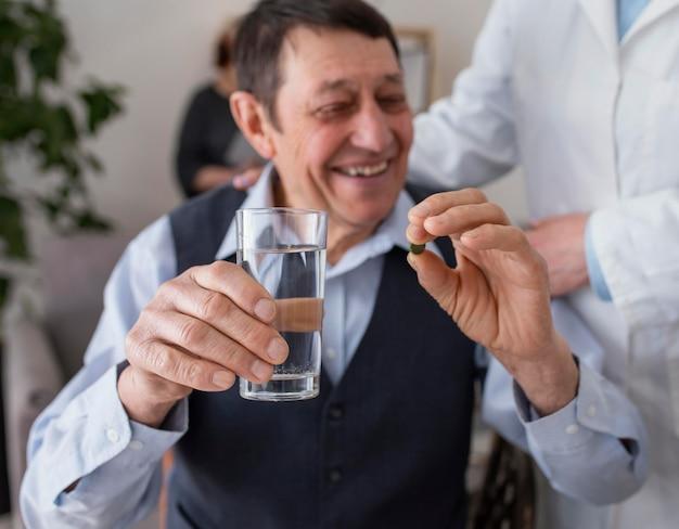 Close-up sorridente homem tomando pílula