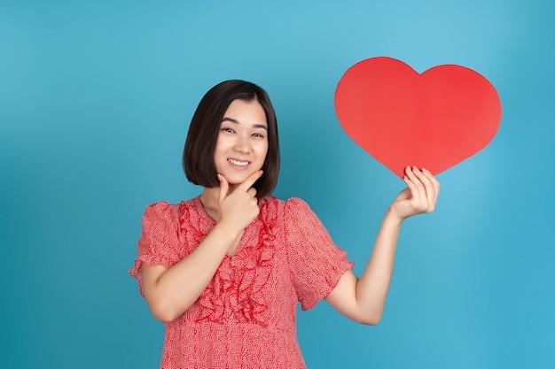 Close-up sorridente jovem asiática com um vestido vermelho segurando um grande coração de papel vermelho e esfregando o queixo com a mão