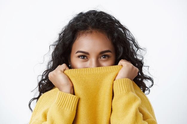 Close-up sorridente menina bonita, cabelo preto encaracolado, puxar o suéter no rosto e sorrindo com os olhos, risadinha brincalhona e sedutora, olhando para a câmera, parecendo bobo na parede branca