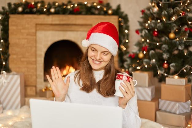 Close-up sorridente mulher europeia usando laptop, olhando para a tela, acenando com a mão, cumprimentando, conversando online com alguém, fazendo videochamada na árvore de natal e lareira