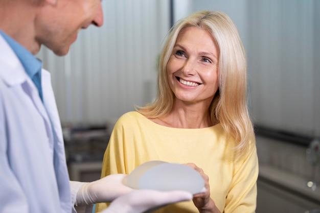 Close-up sorridente mulher segurando implante mamário