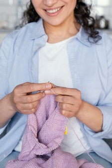 Close-up sorridente mulher tricotando