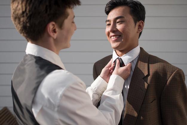Close-up sorridente parceiro arranjando gravata