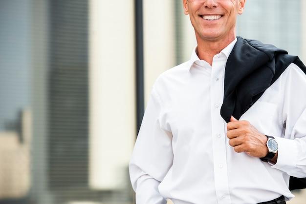 Close-up, sorrindo, homem negócios, perto, vidro, predios