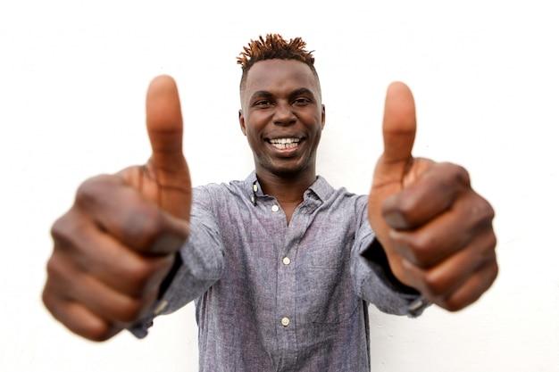 Close-up sorrindo jovem afro com dois polegares para cima no fundo branco