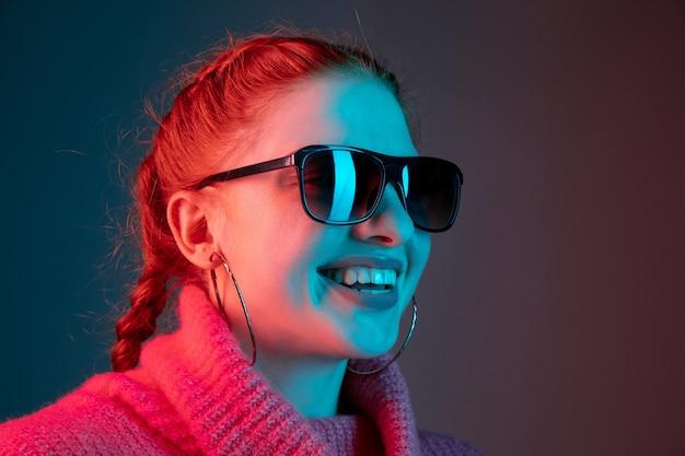 Close up, sorrindo. retrato da mulher caucasiana isolado no fundo do estúdio gradiente em luz de néon. linda modelo feminino com óculos escuros, cabelo vermelho. conceito de emoções humanas, expressão facial, anúncio.