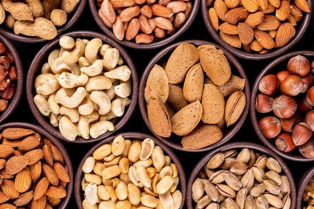 Close-up sortidas nozes e frutas secas em mini tigelas diferentes com nozes, pistache, amêndoa, amendoim, caju, pinhões