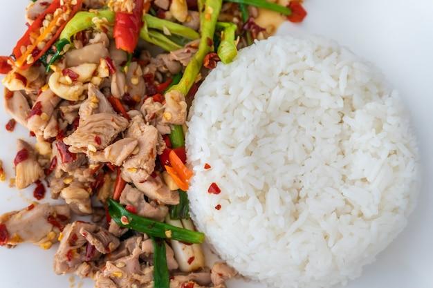 Close-up stir frito frango picado e manjericão com arroz de jasmim na mesa