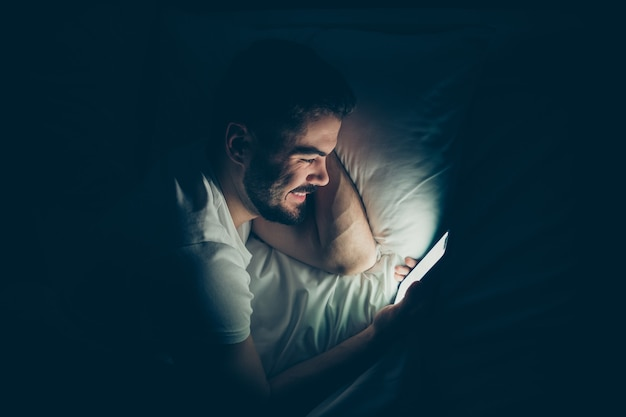 Close-up superior acima da vista de alto ângulo retrato de seu ele agradável atraente alegre alegre rapaz deitado na cama usando o serviço da web para celular conversando online à noite tarde da noite em casa quarto escuro iluminado casa