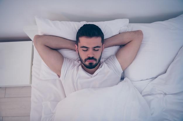 Close-up superior acima da vista de alto ângulo retrato de seu lindo rapaz moreno atraente deitado na cama branca, dormindo pacificamente à noite, tarde da noite em casa, quarto de hotel dentro de casa