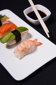 Close-up sushi perto de molho de soja e pauzinhos