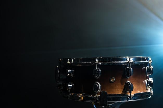 Close-up, tarola em fundo escuro com holofotes de palco, copie o espaço.