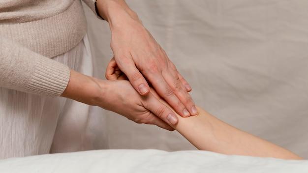 Close-up terapeuta massageando a mão