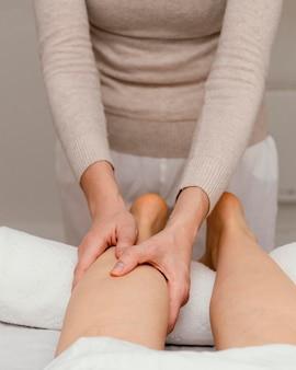 Close-up terapeuta massageando a perna
