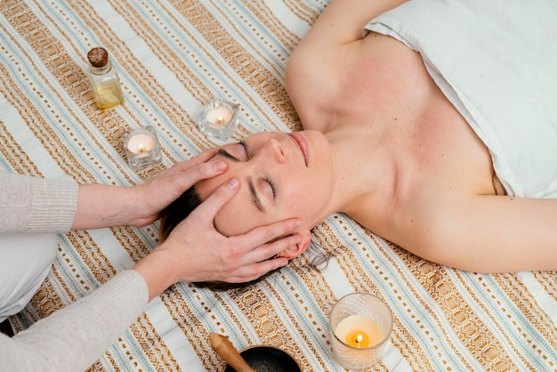 Close-up terapeuta massageando a testa de alto ângulo
