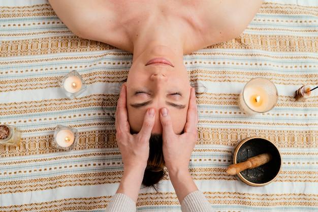 Close-up terapeuta massageando a vista superior da testa