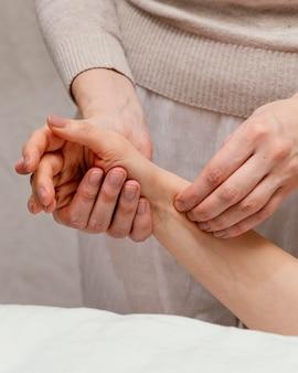 Close up terapeuta massageando o braço