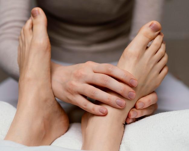 Close-up terapeuta massageando o pé
