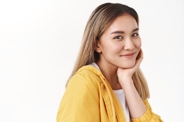 Close-up terno elegante alegre feminino feliz sortudo menina loira asiática virar a câmera meio virada olhar sorridente terno toque pele limpa sem acne satisfeito após tratamento de cosméticos para rosto parede branca